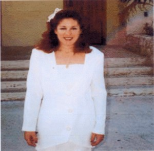 "Lori G. on the day of her Baptism into the Catholic Church in 1992.  Please note the rainbow spectrum above her left shoulder in the photograph.  The rainbow had become her signature, characteristic of her relationship with the Lord. Lori would often request the Lord to send a ""rainbow"" as a means of confirming, that is, a feedback mechanism assuring her that the messages and directives she was receiving came from him and not the evil one."
